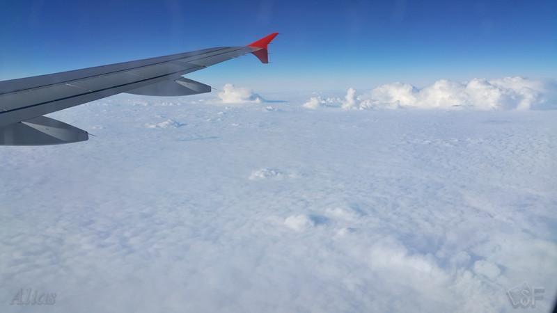 Вид из иллюминатора на облака внизу